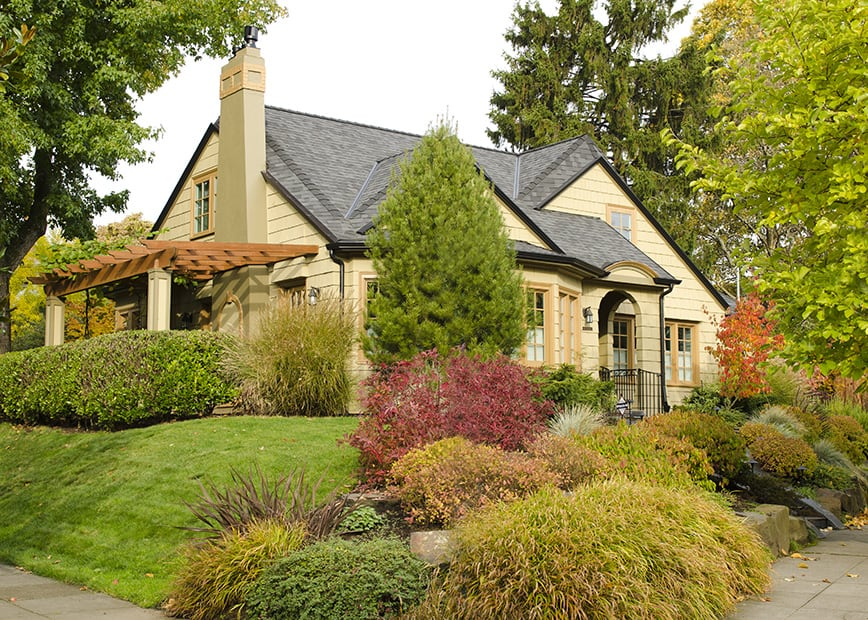 Front of home, lush landscaping, arbor, wrought iron railing