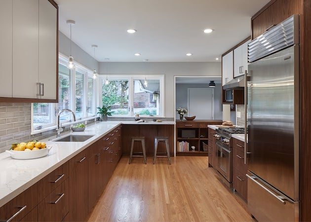 Large galley kitchen, new cabinetry with wood lower and white upper, eating area with stools, pendant lights, book shelves