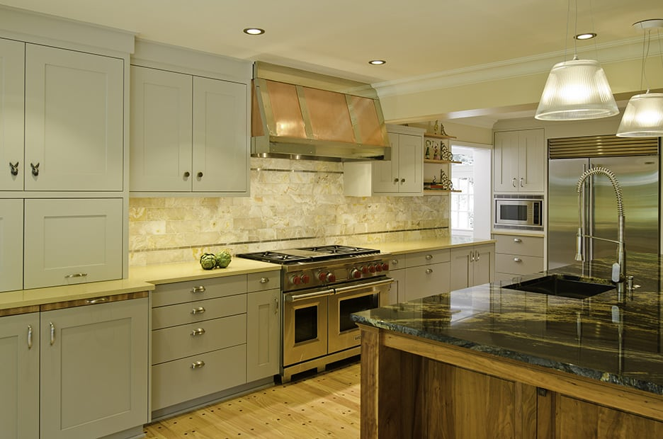Kitchen with large island with slab countertop, new painted cabinets, professional stove