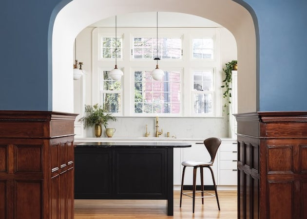 Archway into kitchen, detailed inlay in hardwood floor, extensive wainscot, bright white cabinetry, wooden painted island